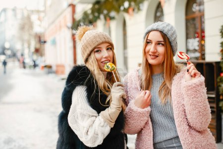 Two young and stylish girls in the winter clothes ...