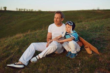 Photo pour Père et fils en costume de pilote avec des ailes assises sur l'herbe au coucher du soleil dans la nature . - image libre de droit
