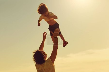 Photo for Father and child playing in nature at sunset. Dad throws his son in the park. Fathers day. - Royalty Free Image
