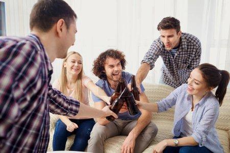 Photo pour Un groupe d'amis claque des bouteilles lors d'une réunion dans la salle . - image libre de droit