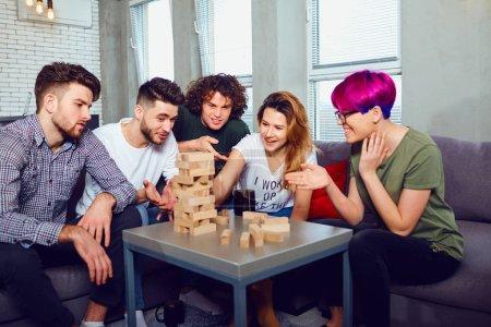 Photo pour Un groupe joyeux d'amis jouent à des jeux de société dans la salle . - image libre de droit
