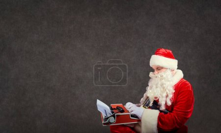 Photo for Santa Claus writes a letter on the a typewriter on gray background. - Royalty Free Image