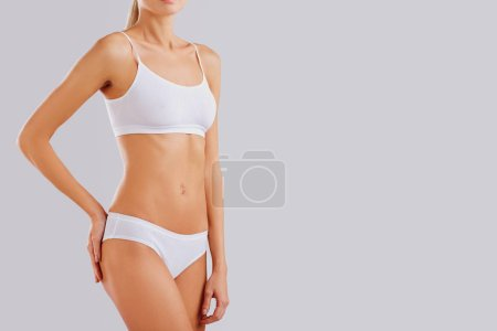 Photo for Slim body of a young woman in lingerie on a gray background. - Royalty Free Image