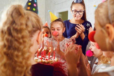 Foto de Una celebración de cumpleaños de los niños. Grupos de niños niñas con un pastel de risa en el interior. - Imagen libre de derechos