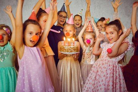 Foto de Los niños con una tarta de cumpleaños divertirse en una fiesta de cumpleaños. - Imagen libre de derechos