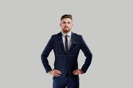 Photo pour Bel homme d'affaires sérieux en costume élégant debout avec les mains sur la taille en regardant la caméra - image libre de droit