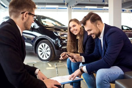 Photo for Buying a new car. Signature of the contract for the purchase of cars in the showroom. - Royalty Free Image