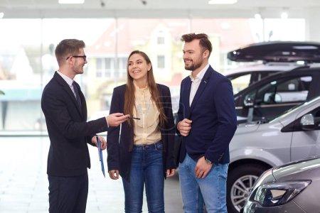 ein Mann und eine Frau kaufen ein Auto.