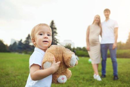 Photo pour Petit garçon charmant avec ours en peluche debout sur la prairie verte avec mère enceinte heureuse et père sur fond - image libre de droit