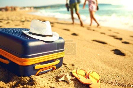 Photo pour Le concept de vacances d'été au bord de la mer. Valise et chapeau sur la plage de sable de la mer . - image libre de droit
