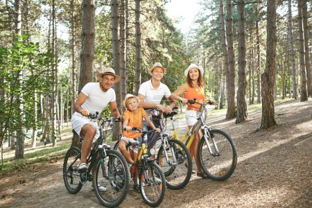 Photo for Happy family on bicycles for a walk in summer park. - Royalty Free Image