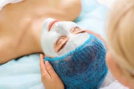 Photo pour Cosmetologue fait masque de beauté à une jeune femme dans un salon de beauté . - image libre de droit