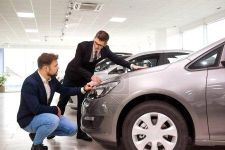 Photo pour Client et vendeur choisissent une voiture dans le showroom . - image libre de droit