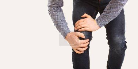Photo pour Traumatisme, douleur, genoux. Rupture ligamentaire. Rupture du ménisque. Un homme tient son genou avec une main sur un fond gris . - image libre de droit