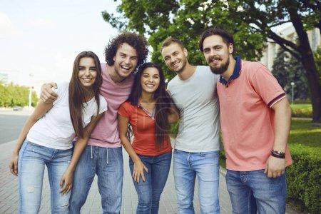 Photo pour Groupe de personnes souriant debout dans une rue de la ville en été. Amis câlins à une réunion . - image libre de droit