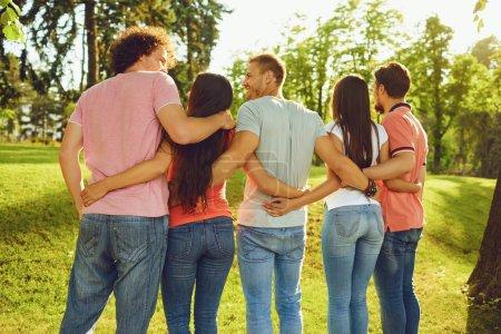 Foto de Grupos de amigos son abrazados en el parque en la naturaleza. Vista trasera . - Imagen libre de derechos