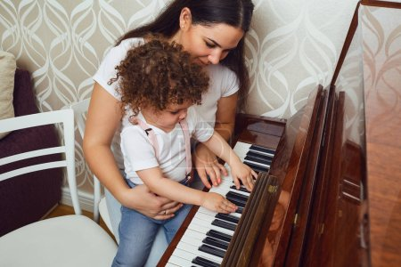 Photo for Mother teacher teaches the child to play the piano. Piano lesson. - Royalty Free Image