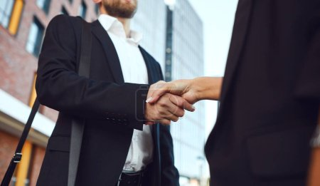 Handshake business. Businessman and business woman make handshakes while standing outdoors