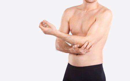 Photo pour Blessure au coude. Douleur au coude. Un homme tient un coude avec sa main sur un fond gris . - image libre de droit