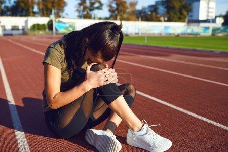 Photo pour Blessure au genou à l'entraînement. Une fille s'est blessé à la jambe pendant l'exercice. Blessure en courant. Douleur au genou . - image libre de droit