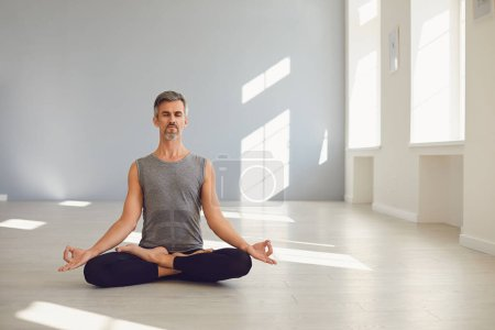 Photo for Yoga man is practicing yoga in a lotus position sitting on a gray floor in a white bright studio. The concept of an active lifestyle of sports life sports yoga pilates meditation relaxation relaxation - Royalty Free Image