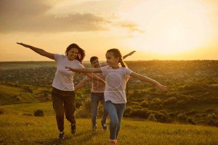Photo pour Bonne famille amusez-vous à courir sur la nature au coucher du soleil. Liberté Voyage Aventure Bonheur Style de vie Concept. Mère père et bébé jouent dans le parc. - image libre de droit