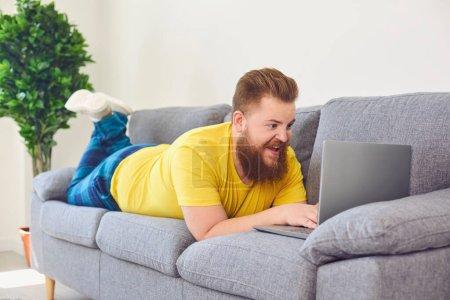 Photo pour Homme gras drôle travaillant achats en ligne rétrécissement regarder une vidéo à la maison dans la chambre. Travail en ligne au bureau à domicile . - image libre de droit