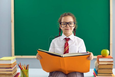Photo for Back to school. Clever schoolgirl in glasses with a book in her hands sitting on the background of the school blackboard. First time at school. Learning education lesson lecture for children students. - Royalty Free Image