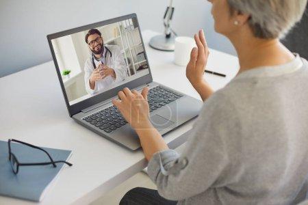 Photo pour Concept de cybermédecine. Femme mûre parlant à son médecin en ligne de la maison. Médecin spécialiste consultant patient aîné sur webcam - image libre de droit