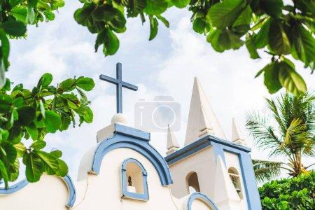 Photo pour L'extérieur d'une petite église Saint Francisco de Assis situé dans l'état Bahia du Brésil, dans la station Praia do Forte ; avec croix en bois bleu sur le dessus, la chapelle avec la cloche et le cadre de feuilles - image libre de droit