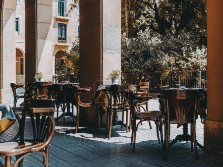 Photo pour Café extérieur confortable avec des tables en bois vides recouvert d'une nappe avec des pots de fleurs en métal et des cendriers dessus, chaises près ; extérieur d'un bar de rue vide le jour attendant ses visiteurs - image libre de droit