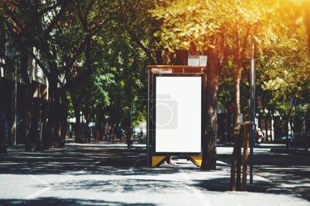 vertikal leere Plakatwand Platzhalter Vorlage auf der Stadt Bushaltestelle mit dem Bürgersteig auf der linken Seite; leere Werbebanner Attrappe in städtischen Einstellungen; weiße leere Informationstafel auf der Straße