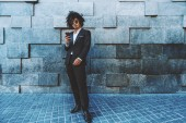 A stylish Asian guy in a formal suit with curly afro hair is standing in front of a textured wall and holding the smartphone; young Japanese businessman with the cell phone near the wall of blacks