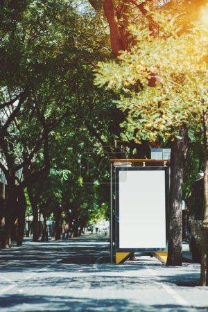 die Plakatwand Platzhalter Vorlage außerhalb der Stadt Bushaltestelle, der Bürgersteig auf der linken Seite; vertikale leere Werbebanner-Attrappe in städtischen Einstellungen; weiße leere Informationstafel auf der Straße