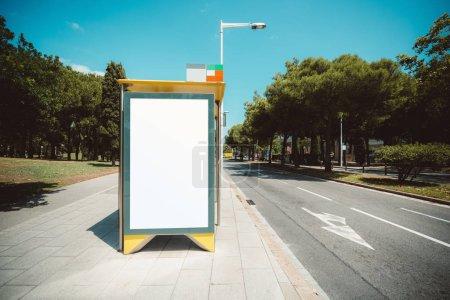 Leere Plakatwand Platzhalter-Vorlage an der Stadtbushaltestelle mit dem Bürgersteig auf der linken Seite; leere Werbebanner-Attrappe in städtischen Umgebungen; weiße leere Informationstafel in der Nähe der Straße