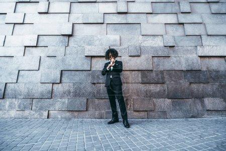 Photo pour Vue grand angle d'un bel homme asiatique bouclé dans un costume formel et des lunettes de soleil debout à l'extérieur devant un mur contemporain de blocs de différentes tailles et rebords ; homme d'affaires dans la rue - image libre de droit