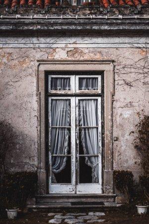 Photo pour Vue verticale d'un porche antique avec un cadre de peinture en bois pelant et de vieux rideaux de dentelle blanche à l'intérieur, entouré par le mur avec du plâtre partiellement écaillé ; l'architecture typique de Sintra, Portugal - image libre de droit