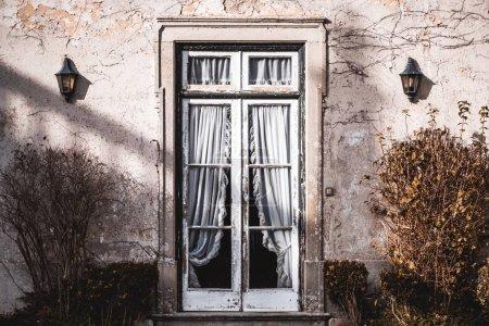Photo pour Une belle vue symétrique d'une véranda antique à l'extérieur avec deux vieilles lanternes sur le mur avec du plâtre partiellement écaillé et une porte en verre au centre avec des rideaux en dentelle à l'intérieur, deux buissons sur les côtés - image libre de droit