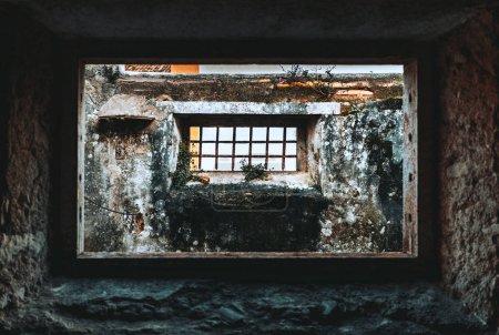 Photo pour La vue depuis la chambre sombre et désolée en pierre à travers le trou de fenêtre d'un ancien porche extérieur abandonné avec une autre fenêtre rectangulaire avec des barres de fer dessus, Sintra, Portugal - image libre de droit