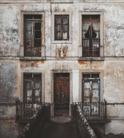Photo pour Une vieille façade sombre d'un bâtiment antique à Sintra, Portugal, avec la porte et cinq fenêtres, le mur avec du plâtre écaillé, un pont en pierre au premier plan qui suit à la porte principale - image libre de droit