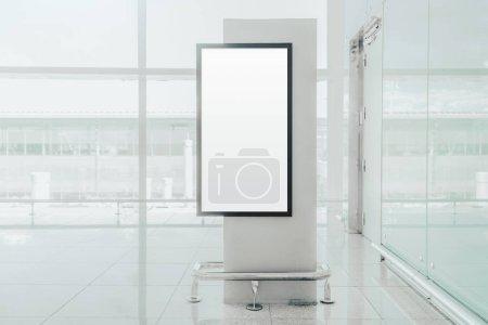 Photo pour Affiche vierge verticale maquette à l'intérieur d'un aérogare ; gabarit d'espace réservé à la bannière d'information vide à côté d'une fenêtre d'un centre commercial ; maquette de panneau d'affichage blanc intérieur à l'intérieur d'un dépôt de gare - image libre de droit