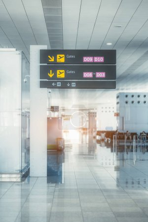 Photo for A long bright empty hall in a departure area of a modern airport terminal leading to boarding gates; a signpost with arrows in the foreground, the waiting halls in a defocused background - Royalty Free Image