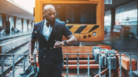 Photo for An elegant bald bearded African man entrepreneur in a vest is checking the departure time for his business trip on his watch while waiting in front of a high-speed train locomotive on the platform - Royalty Free Image