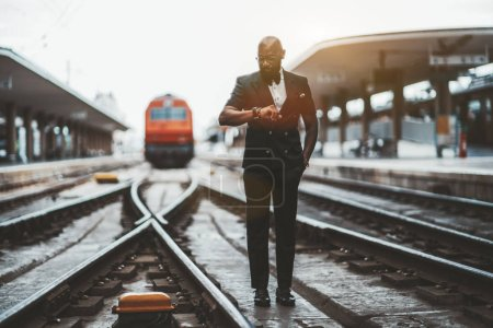 Photo for A fancy bald bearded African man entrepreneur in glasses and a vest is checking the departure time while standing  between platforms on the railroad track in front of a red high-speed train locomotive - Royalty Free Image
