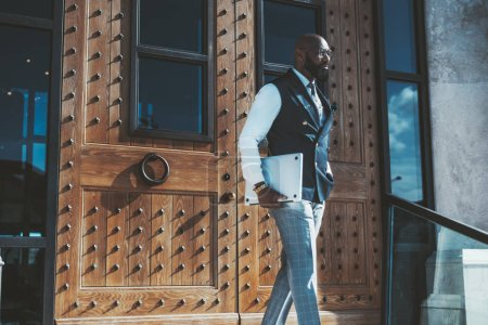 Photo for An elegant bald bearded African man entrepreneur in eyeglasses and vest has just left a modern building after a business meeting and coming downstairs while carrying a laptop in his hand - Royalty Free Image