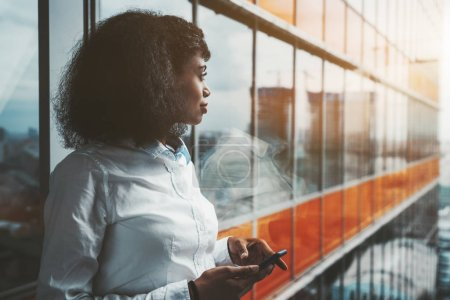 Photo for A dazzling young African-American woman entrepreneur with a cellphone in her hands is standing next to a panoramic window of a modern office skyscraper with orange lines and pensively looking outside - Royalty Free Image