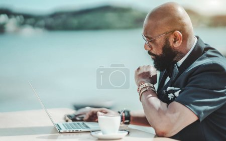 Photo for An elegant African man entrepreneur in glasses wand vest is using his modern laptop while having a coffee break in an outdoor cafe; a fancy black bald bearded man in a street bar is using a netbook - Royalty Free Image