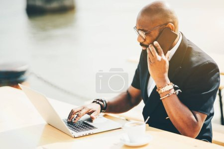Photo for A mature bald African man entrepreneur in eyeglasses is having a coffee break in an outdoor cafe near water, using his laptop and speaking on the phone; a cup of delicious coffee drink on the table - Royalty Free Image