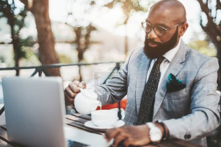 Photo for Elegant mature bald African businessman with a neat beard, in eyeglasses and a formal costume, is having business lunch in an outdoor cafe and pouring tea into a cup, an opened laptop in front of him - Royalty Free Image