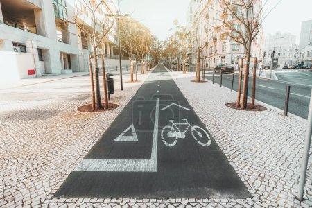 Photo pour Plan grand angle d'une piste cyclable asphaltée et d'une piste de course en milieu urbain entourée de pavés et de jeunes arbres, de maisons résidentielles et d'une route avec voitures, journée ensoleillée, Lisbonne, Portugal - image libre de droit